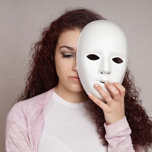 sad woman hiding behind mask