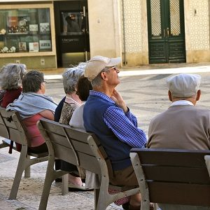 Older men and women sitting on a seat in a piazza