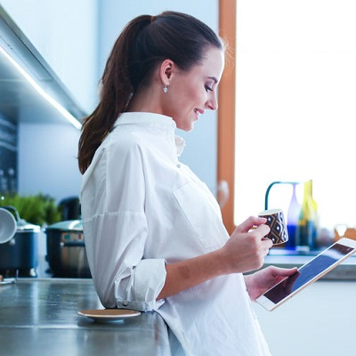 Young woman using tablet in kitchen at home and drinking coffee