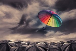 Change Concept Colorful umbrella flying over black umbrellas