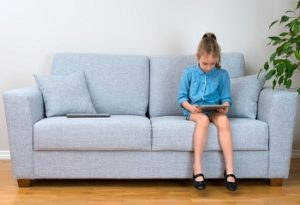 girl sitting on sofa playing game on tablet