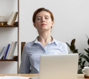 worker at home office stretching neck and shoulders