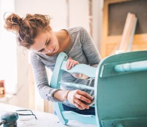 things to do -woman restoring wooden chair as business
