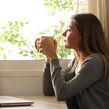 Relaxed woman thinking and drinking coffee