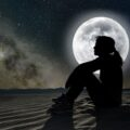 woman sitting on sand in the moonlight