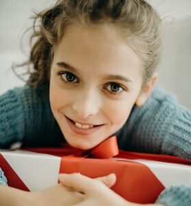 Smiling teenager holding boxed gift