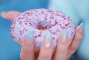Woman holding iced donut