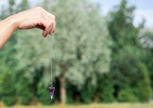 woman holding purple amethyst pendulum
