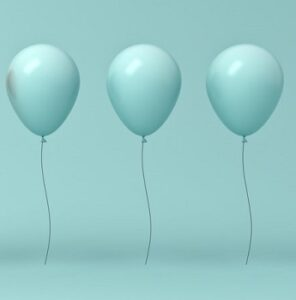 three green balloons part of the crowd concept